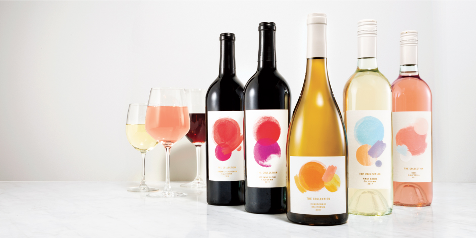 Five assorted bottles of wine from The Collection sit on a counter beside three glasses of wine