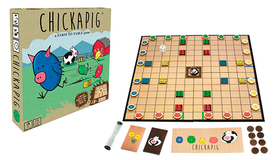 The Chickapig board game box sits next to an assembled playing board with cards and pieces