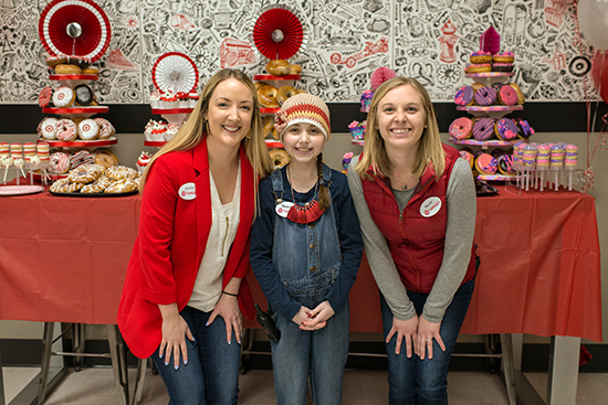 Maddie stands between two team members in front of a table full of colorful treats