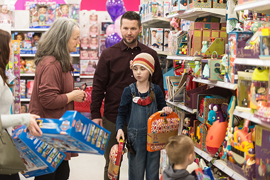 Maddie stands in a Target aisle deciding which toys to choose, with help from team members and family