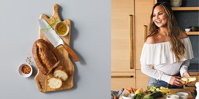 A wooden cutting board displays bread and a knife, alongside an image of Chrissy Teigen cooking