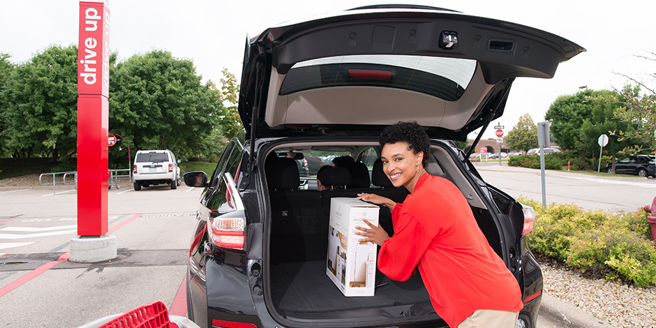 A Target team member places a box in a guests' car