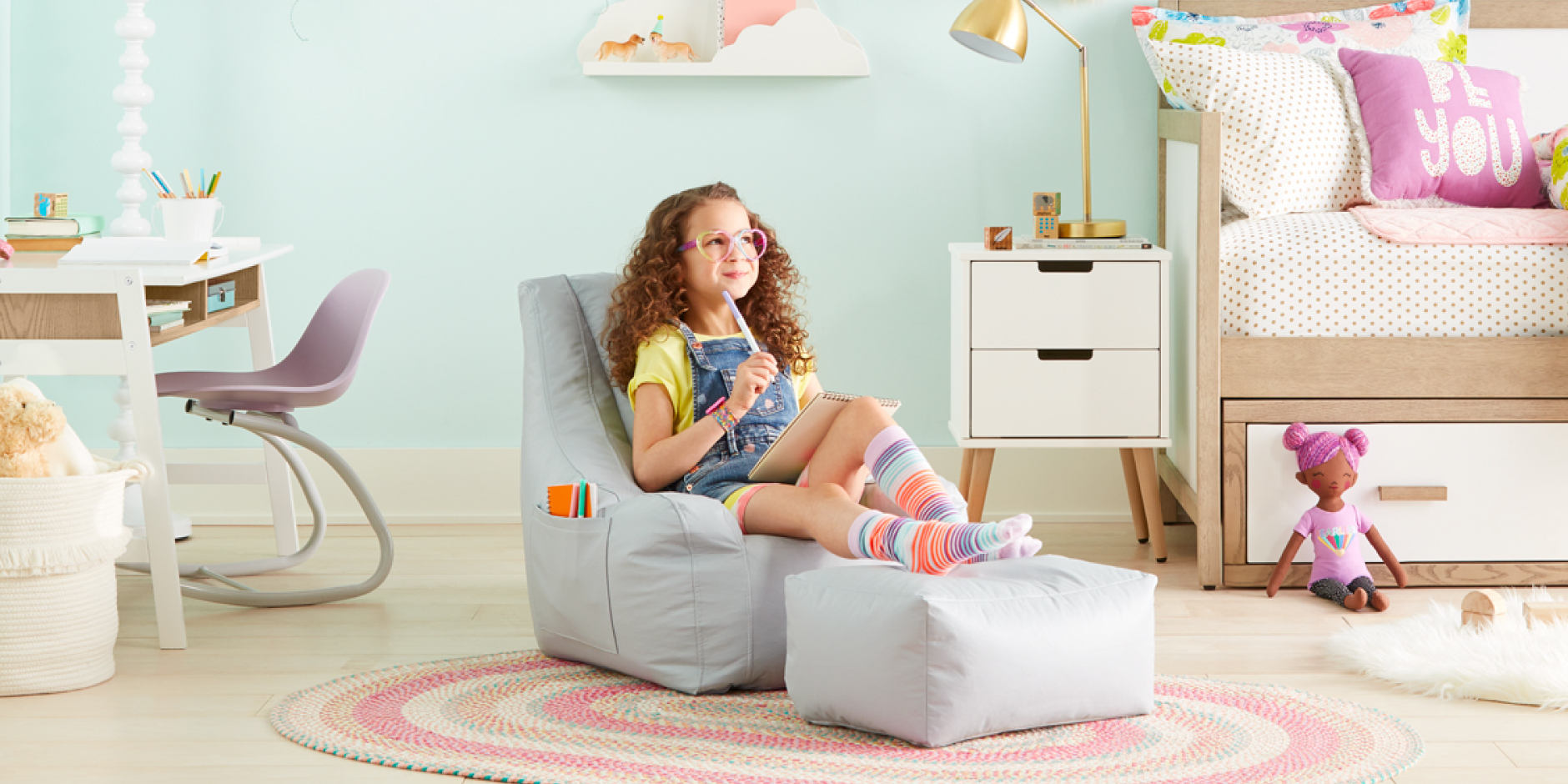 A little girl relaxes on a grey chair within a colorful bedroom