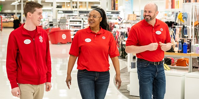 Three team members wearing red shirts walk and talk in a Target aisle