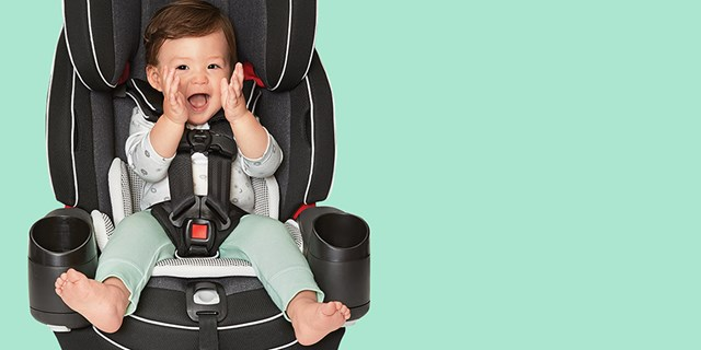 A smiling baby is buckled into a gray car seat against a green background