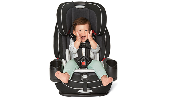 A baby smiles and claps sitting in a gray and black car seat