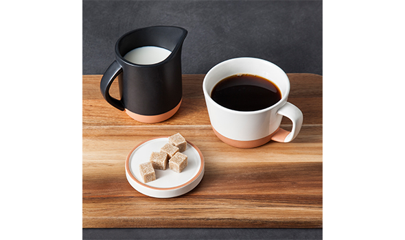 A white coffee mug filled with coffee next to a black pitcher of cream and plate of sugar cubes on a wooden tray