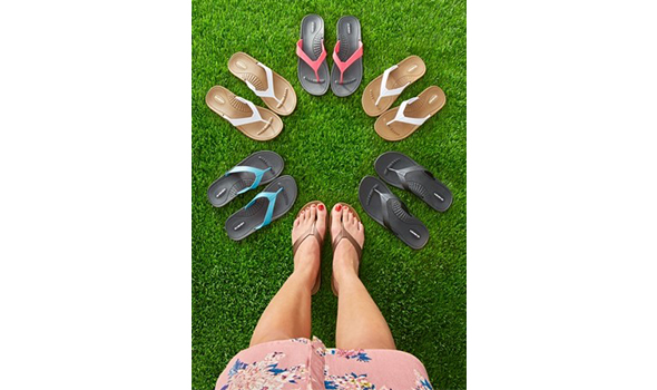 A woman's feet wearing a pair of Okabashi flip flops, with five other pairs arranged in a circle on green grass.