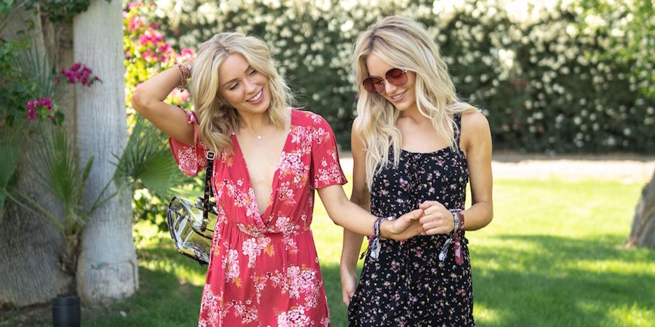 Cassie and Michelle walk together holding hands and wearing floral dresses from Target