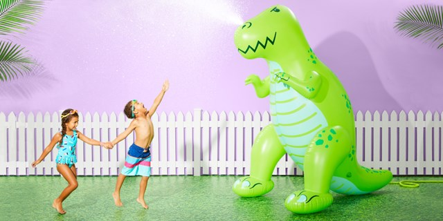 Two kids play near a giant T-rex inflatable sprinkler