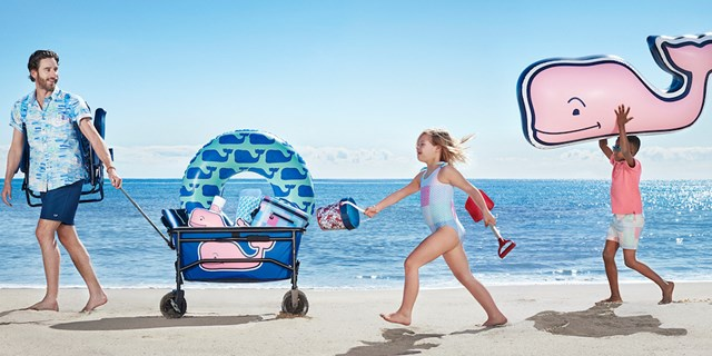An adult and two kids pull a wagon of beach gear across the sand in front of the sea