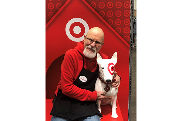 Vyto sits with his arm around a statue of Target mascot Bullseye the dog