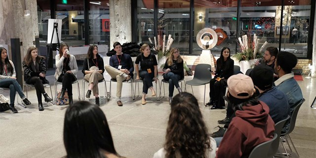Participants and mentors sit in a circle of chairs inside a Target event space
