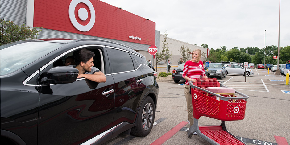 A team member brings a shopping cart to a guest's car