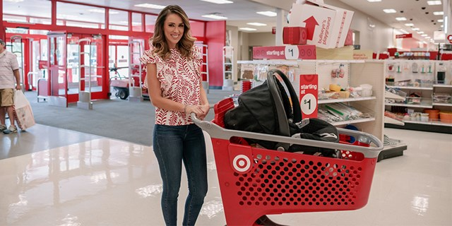 Jacky Bracamontes stands at the entrance of a store with a shopping cart and car seat inside