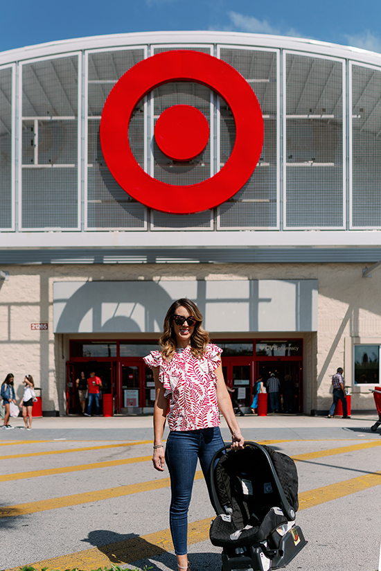 Jacky Bracamontes stands outside a Target store holding a car seat