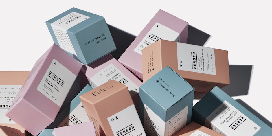 A pile of colorful packages of Versed skin care products against a white background