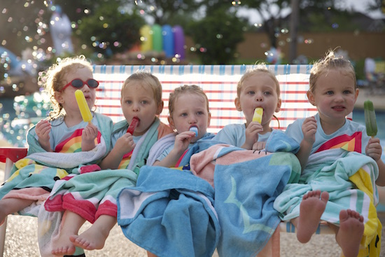The girls enjoy popsicles as they share a foldable bench chair