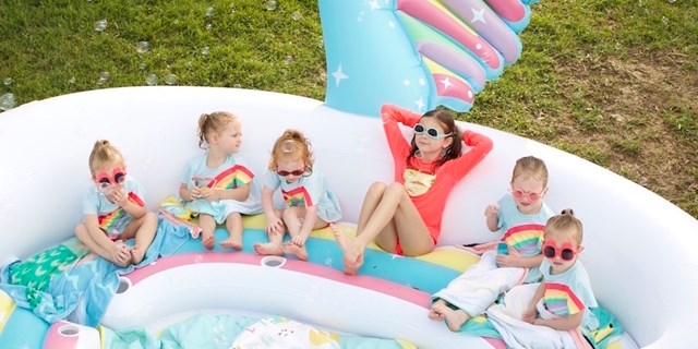 Five toddler girls and one older girl wear sunglasses and relax on a unicorn inflatable