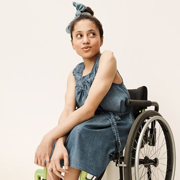 A woman in a wheelchair wears a chambray dress