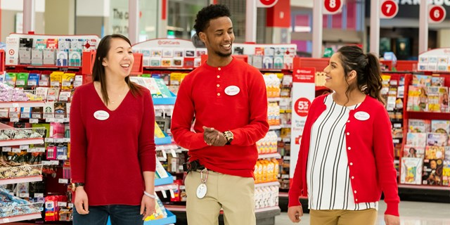 Three team members talking as they walk near the Target checkout lanes