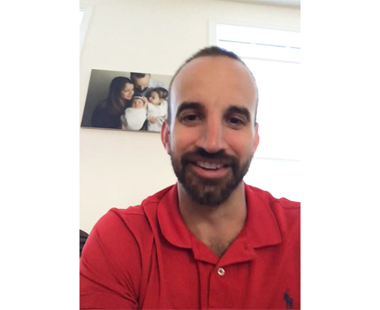 Ryan smiles at the camera, wearing a red shirt in front of a family photo on the wall