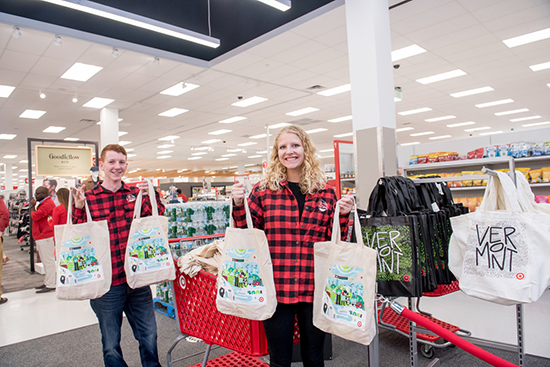 Two team members stand with a shopping cart handing out reusable totes to guests