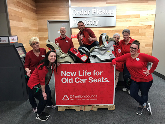 Team members standing around a box of car seat parts collected through the trade-in program
