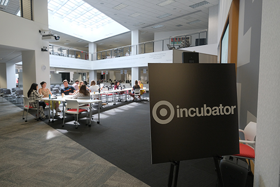 "Participants work at a table in their Target space. A sign in the foreground reads ""Target Incubator."""