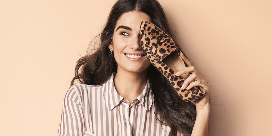 A woman smiles as she holds up a leopard print shoe