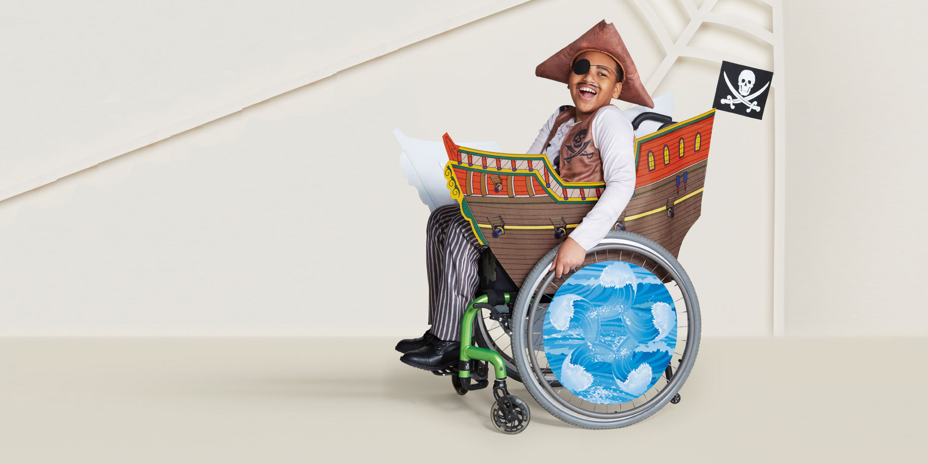 A boy models a pirate costume, his wheel chair decked out like a pirate ship