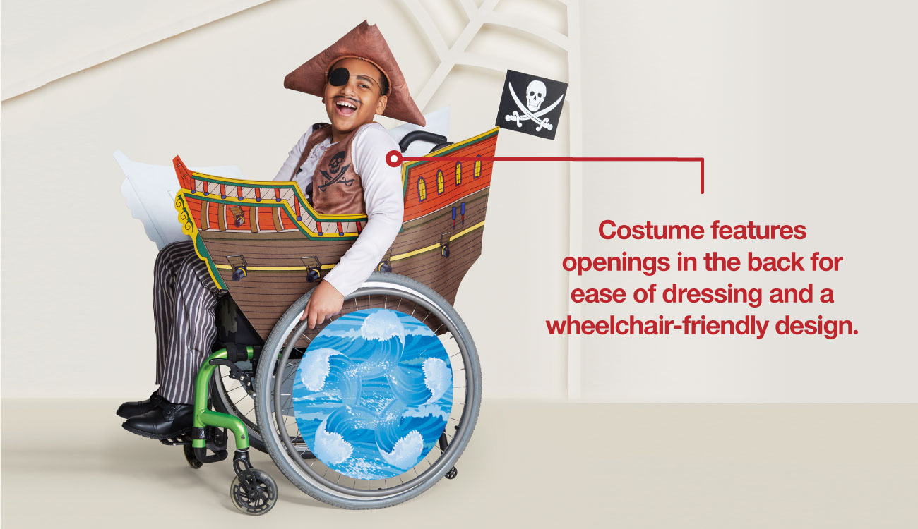 A boy models a pirate costume, his wheelchair decked out like a pirate ship.