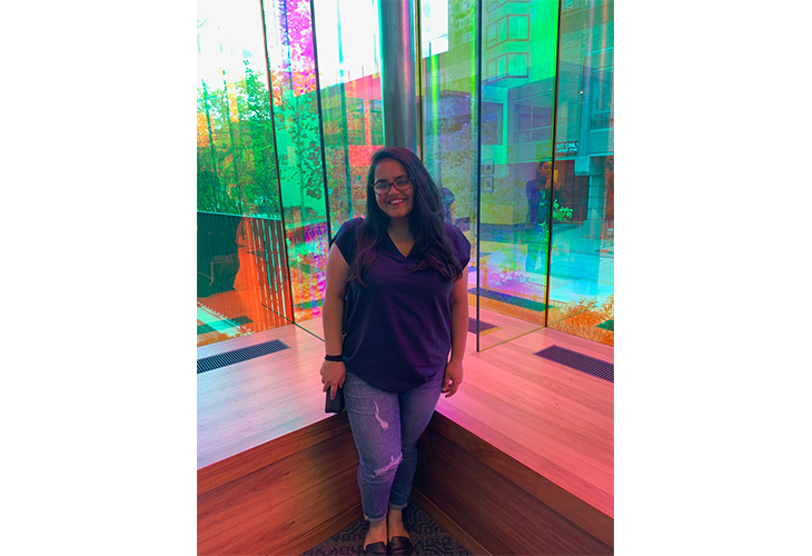 Anushka stands near a multicolored glass window with lights reflecting around her. She's wearing a dark blue top and blue jeans.