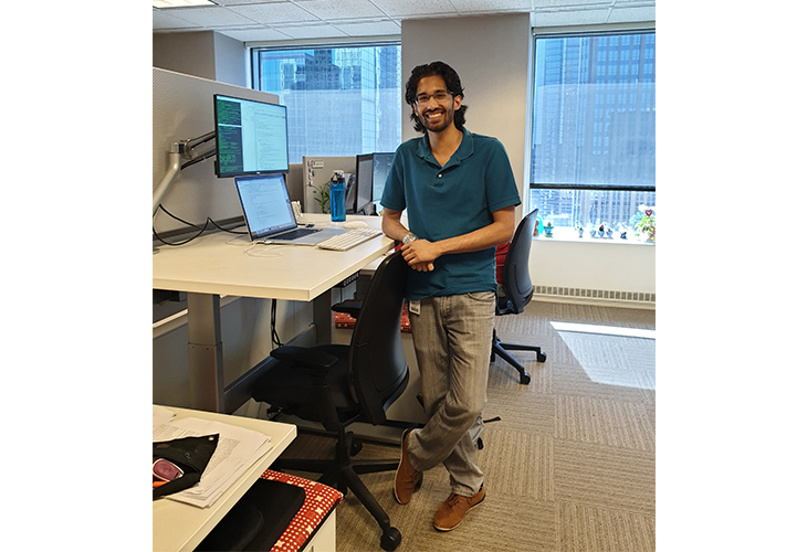 Arjun stands in his workspace with his desk and laptop against an office window. He's wearing a blue shirt and tan pants.
