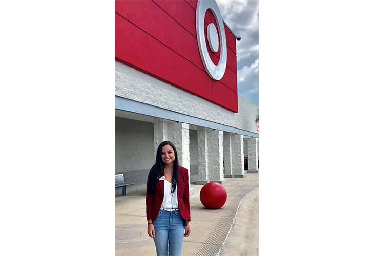 Karina stands outside her Target store wearing a red jacket, white shirt and blue jeans