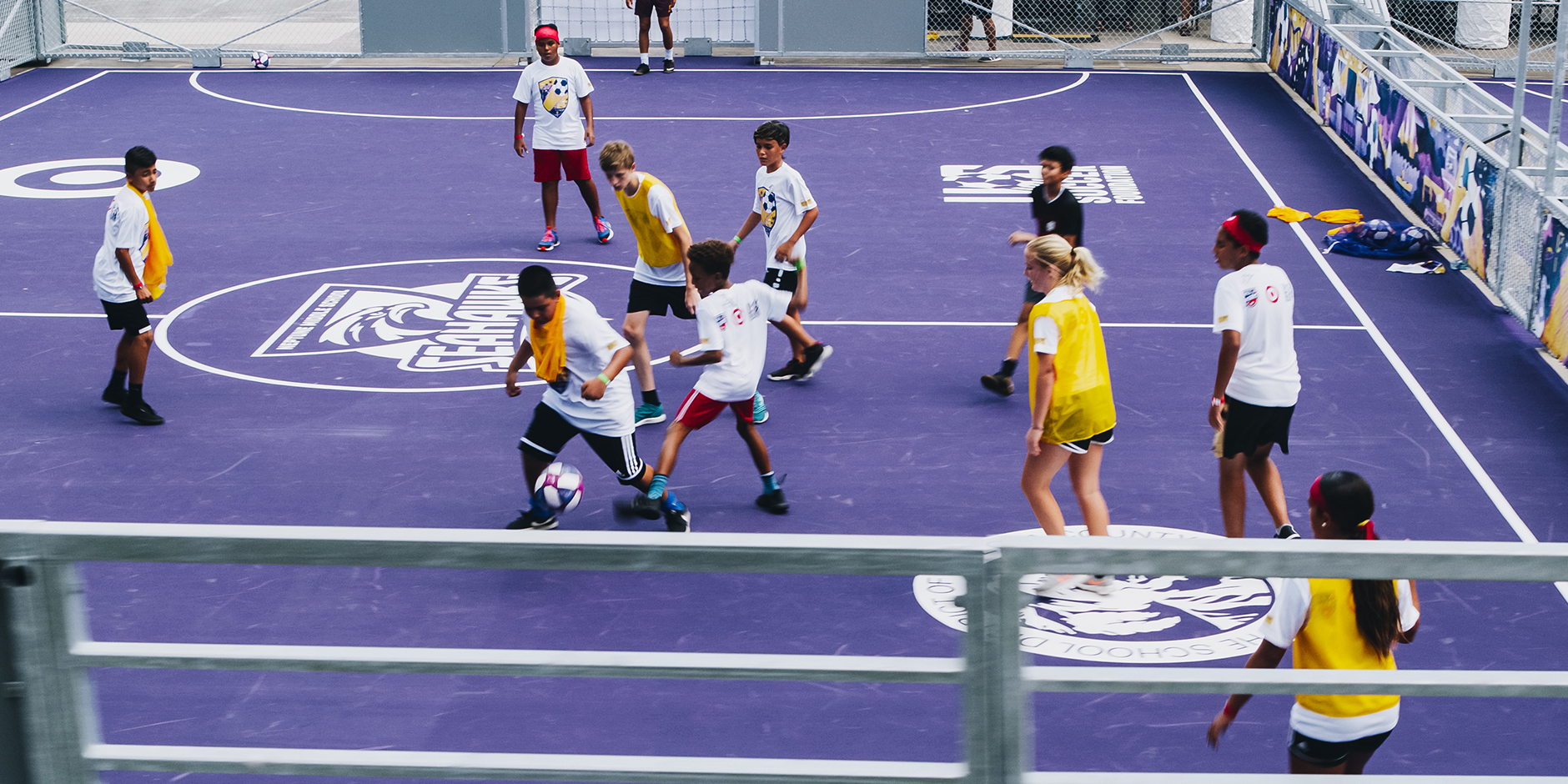 Students play soccer on a purple pitch with bullseye logo
