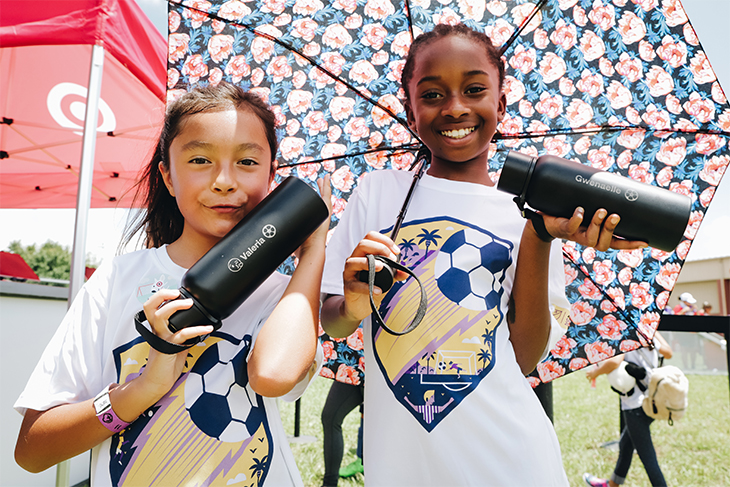 Two teen girls holding a floral umbrella and two black water bottles