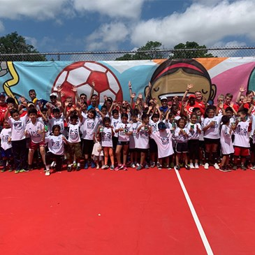 A large group of kids and adults stand on a new red pitch in front of a colorful mural