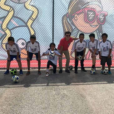 six kids and an adult stand ready to kick soccer balls in front of an illustrated mural
