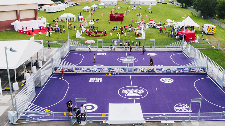 Neptune Middle School's two new purple soccer pitches with community day festivities taking place on a green field behind them