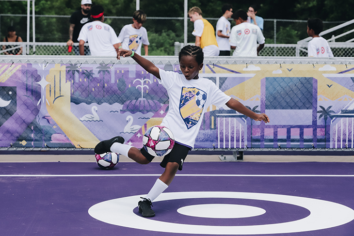 A kid kicks a ball on the purple pitch with a white bullseye logo