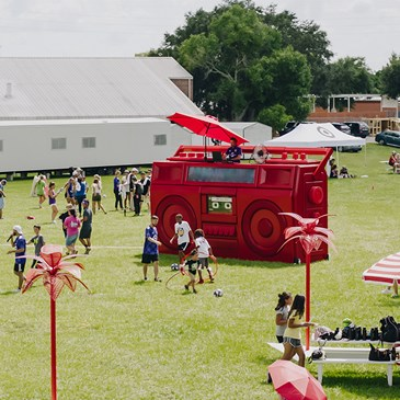 People enjoy the celebration on a green field with a giant red bullseye boombox