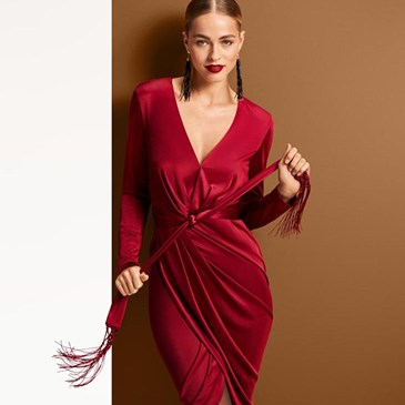 woman in close-fitting red v-neck knee-length dress with ruching and fringe belt