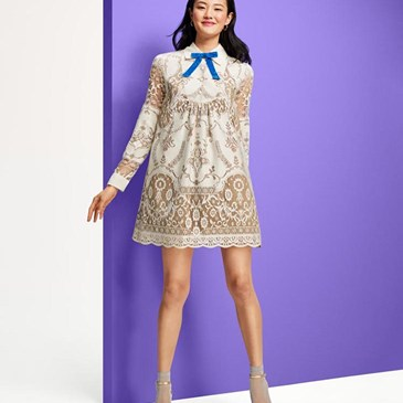 petite woman in white mini dress with gray pattern and blue bow at the neck
