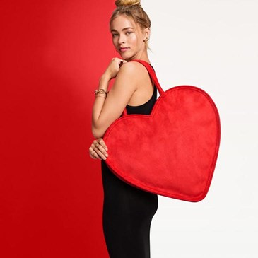 woman facing away from camera holding a big red heart bag