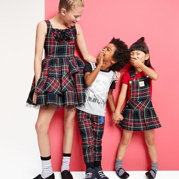 one older child and two younger children smiling, in plaid dresses and pants (black, red, green)