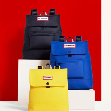 three backpacks on pedestals: black, blue, yellow