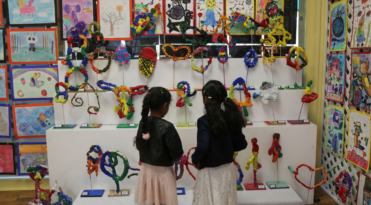Two little girls examine a colorful display of children's art projects