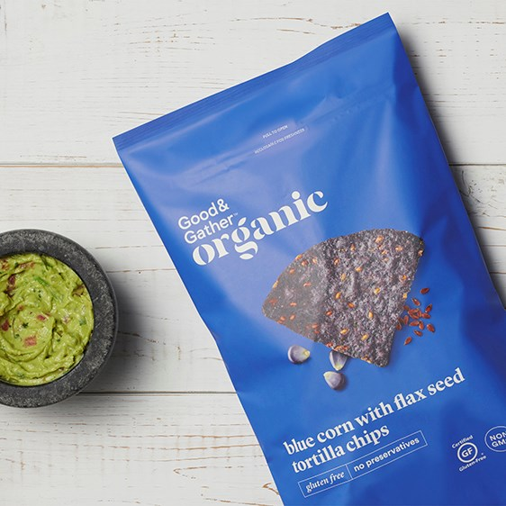 A blue bag of organic tortilla chips with a bowl of guacamole