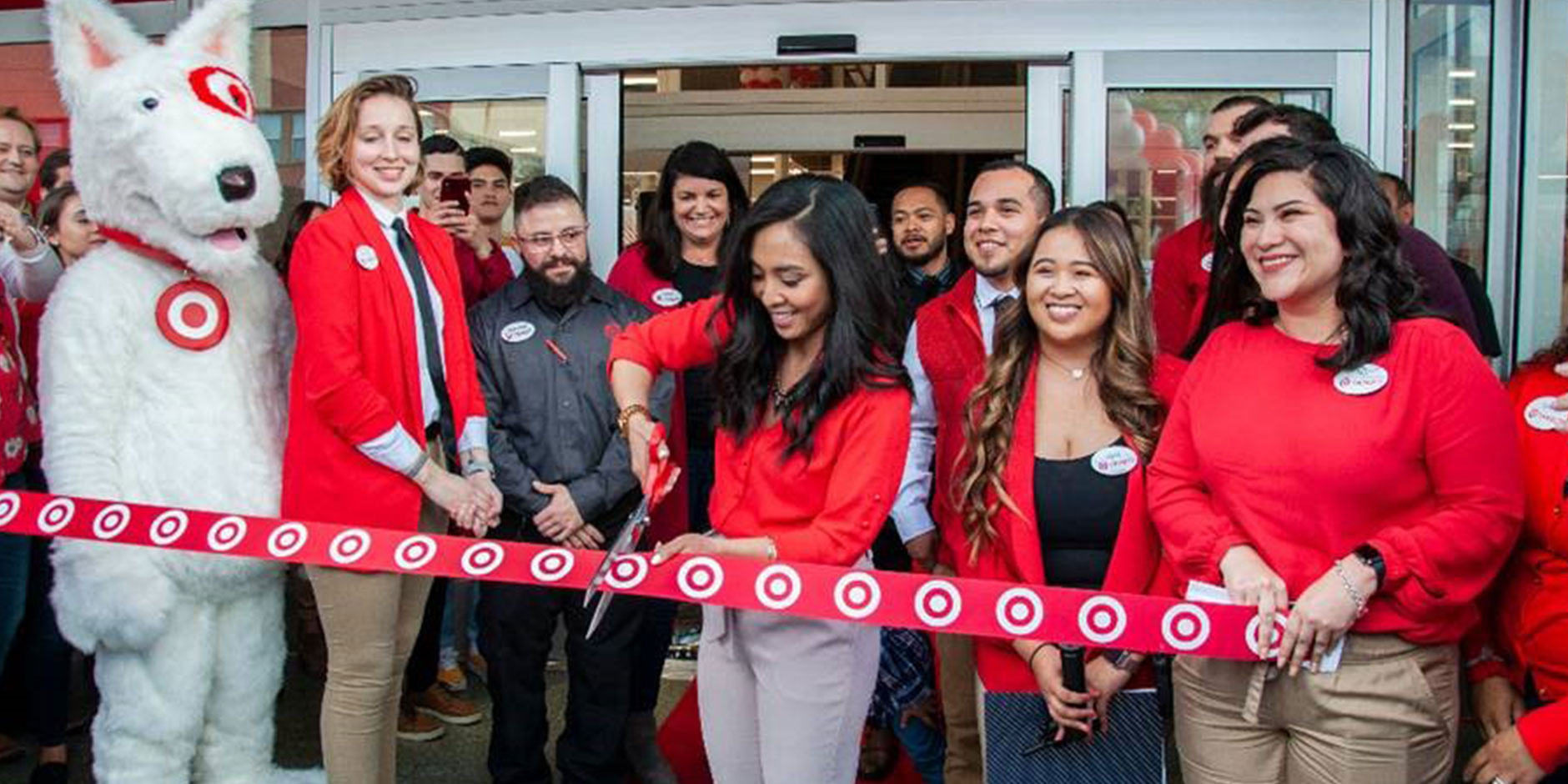 group of Team Members outside a new store while a female cuts a red ribbon with large scissors